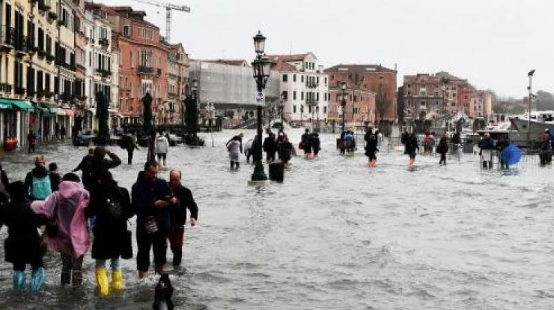 People walk in the flooded street during a high-water alert in Venice. (Photo: AFP)
