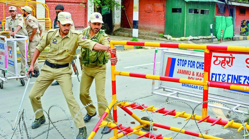 Police personnel block the road near the residences of former chief ministers Omar Abdullah and Mehbooba Mufti in Srinagar on Saturday. (Photo: AP)