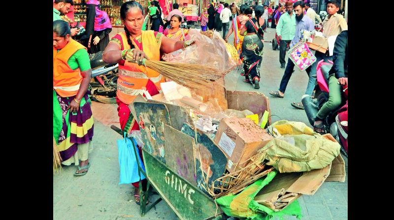 GHMC staff collect garbage from the pavements of Charminar on Tuesday as there are no garbage bins around the monument. (Photo: DC)
