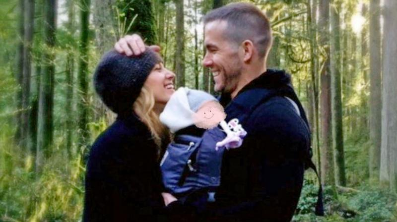 Ryan, whose photo shows him and his wife carrying the baby girl (their third daughter), the Deadpool actor cleverly hid his daughter's face from the camera by putting a drawn-on smiley face on top of hers.