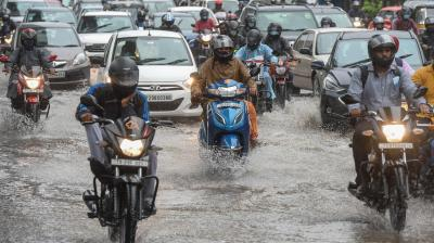 Motorists make their way through a water-logged street amid heavy rains in Hyderabad. (Photo: AFP)