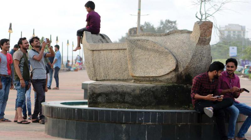 Art for comfort sake: A group of youngsters take the photograph of a child who is  sitting over a sculpture at Beach, Kozhikode.