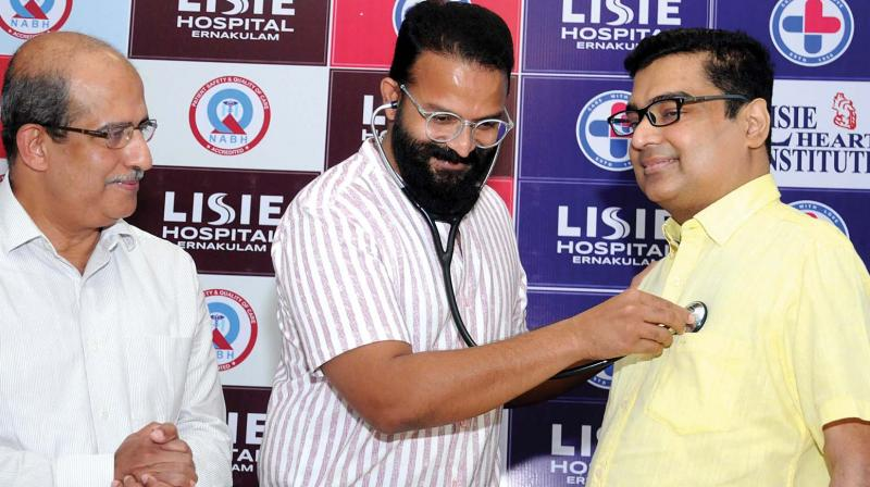 Actor Jayasurya tries a steth he borrowed from Dr Jose Chacko Periyapuram to check on heartbeats of Girish Kumar, who had undergone two heart transplants, at the event marking his fifth year after surgeries at Lisie Hospital, in Kochi on Wednesday.    (ARUN CHANDRABOSE)