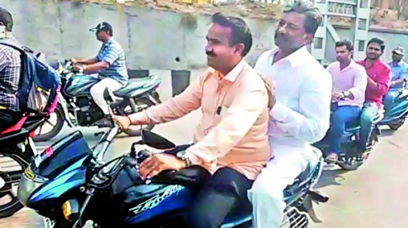 Telangana state excise minister T. Padma Rao rides pillion on his friend's bike in the city on Tuesday. (Photo: DC)