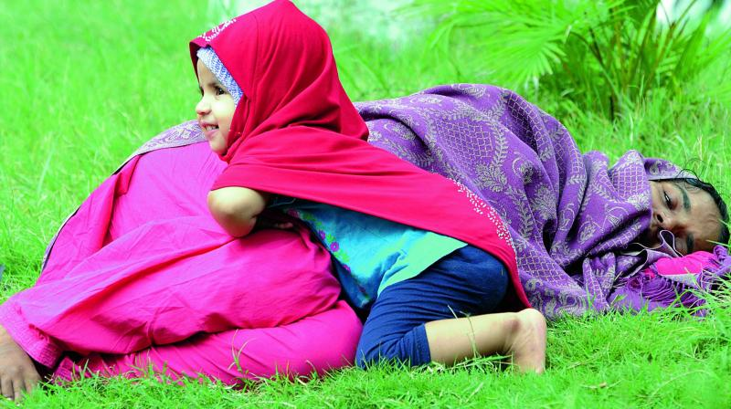 While the mother, who is down with viral fever, lies on the lawn of Fever Hospital awaiting treatment, her daughter happily plays around her mother. 	(Photo: Deepak Deshpande)