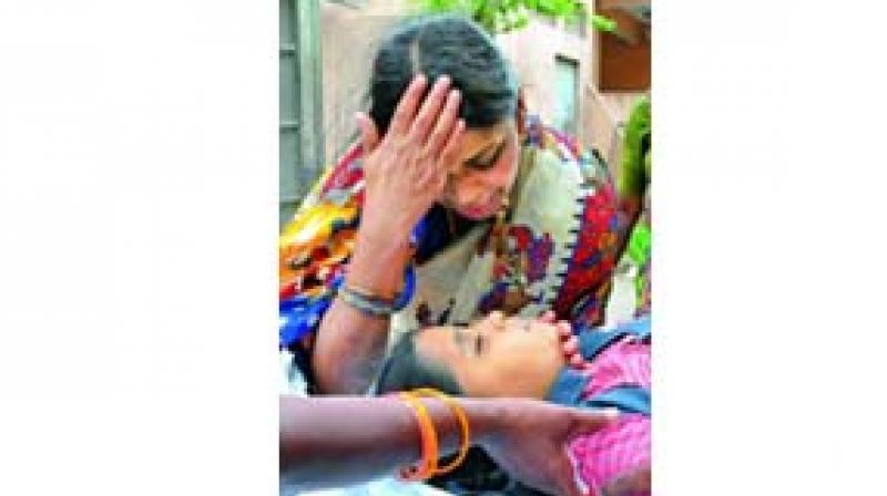 The mother of Veevika, the Class 10 student, who died after a fall from the terrace of of school building, wails over her body.