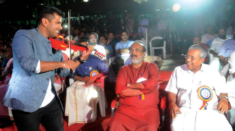Violinist Balabhaskar performs as Finance Minister T. M. Thomas Isaac and Chief Minister Pinarayi Vijayan look on during the first anniversary celebration of the LDF government at Nishagandhi in Thiruvananthapuram on Thursday . (Photo: A.V. MUZAFAR)