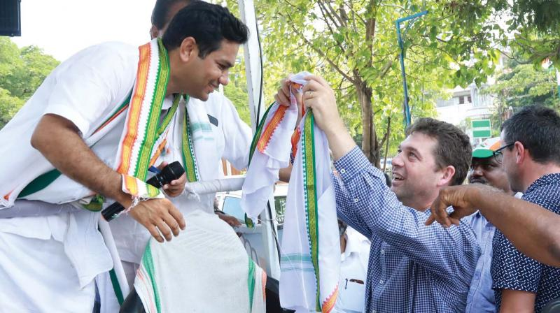 Nick Wakeling, Liberal Party member of the Victorian Legislative Assembly  draping a shawl on Hibi Eden during his election campaign in Vennala on Wednesday in Kochi.