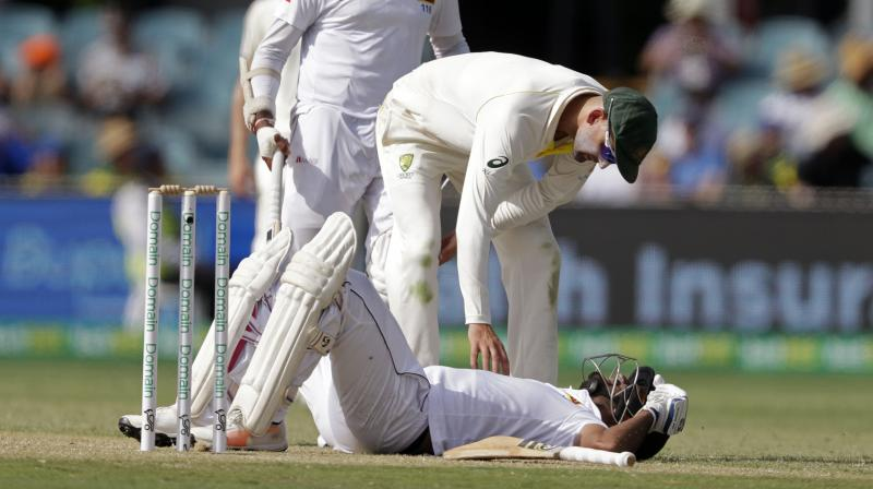 Australia's Nathan Lyon bends over to check on Sri Lanka's Dimuth Karunaratne after he was struck in the head by a delivery from Pat Cummins on day 2 of their cricket test match. (Photo: AP)