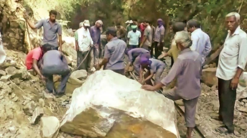 Officials and workers removing the boulders that had fallen on the NMR track near Hillgrove, near Coonoor.