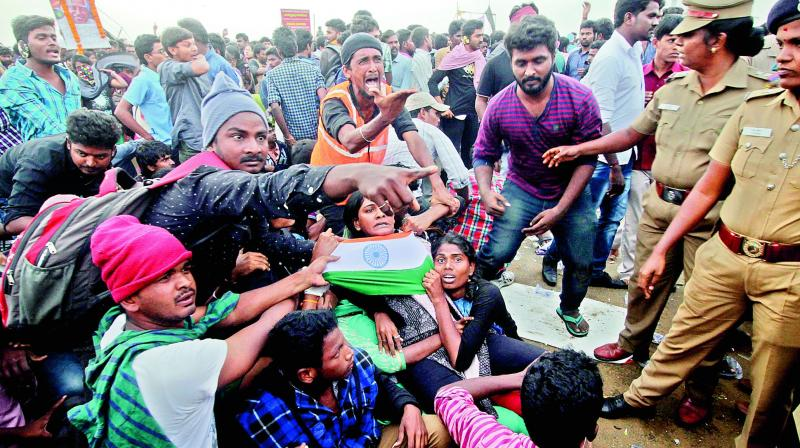 Protesters supporting jallikattu try to hold on to each other as police try to remove them from the Marina beach in Chennai on Monday. Protesters attacked a police station with stones and set some vehicles on fire on Monday in anger at being forcibly evicted from the beach where they been protesting for the past week in support of the sport. (Photo: AP)