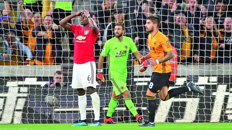 Manchester United's Paul Pogba (right) reacts after his penalty was saved by Wolverhampton goalkeeper Rui Patricio in the English Premier League match at the Molineux Stadium in Wolverhampton on Monday. (Photo: AP)