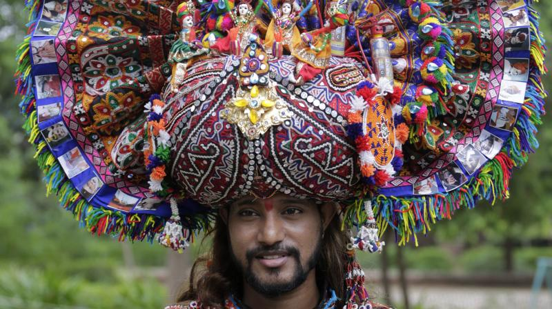 A man sports a colourful headgear with traditional motifs. (Photo: AP)