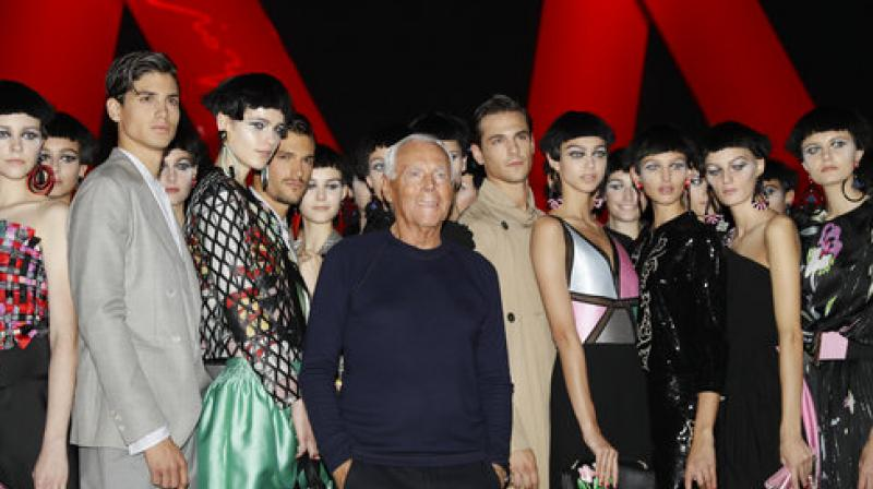 Designer Giorgio Armani, centre, poses with models at the end of his womens Fall/Winter 2018/19 fashion collection, presented in Milan, Italy, Friday, Sept. 22, 2017.