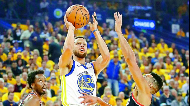 ce1964a5d053 Stephen Curry of the Golden State Warriors shoots the ball against CJ  McCollum (right)