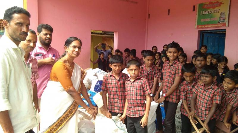 Students hand over scrap items collected from their houses to the District Panchayat officials.