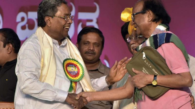 Former CM Siddaramaiah with writer Chandrashekara Patil at Kannada Sahitya Sammelana in Dharwad on Sunday 	– KPN