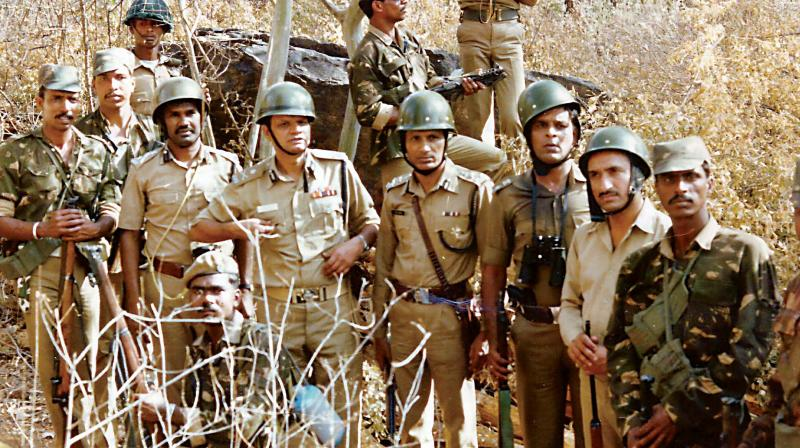 Forest and police officials after the seizure of 65 metric tonnes of sandalwood at Silvekal in Kollegal Division on February 22, 1990.