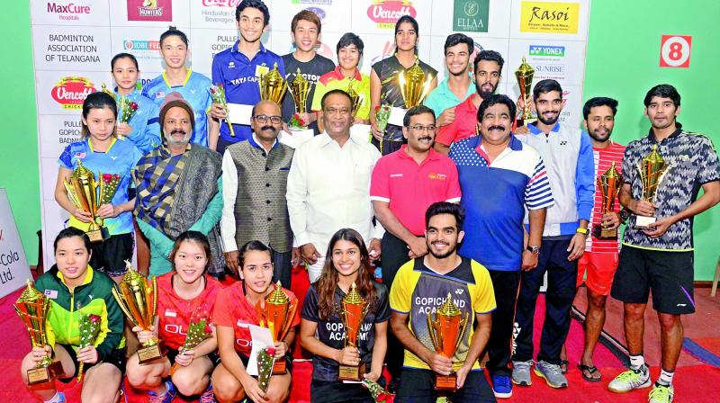 Winners and runners up are all smiles as they pose with their trophies in the India International Series badminton championship on Sunday. Also seen in the pictures are Sports Authority of Telangana State officials.