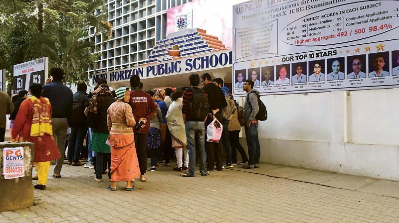 Parents queue up outside New Horizon Public School in Indiranagar on Saturday