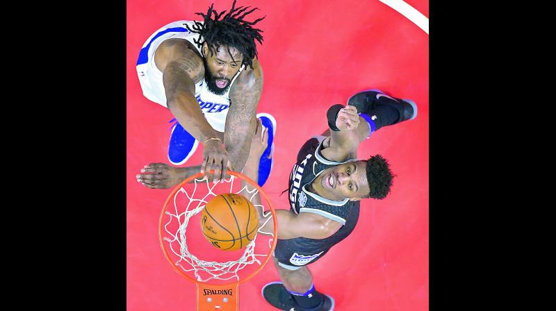 LA Clippers' centre DeAndre Jordan dunks over Sacramento Kings forward Justin Jackson during their NBA basketball game in Los Angeles on Tuesday. The Clippers won 122-95. 	(Photo: AP)