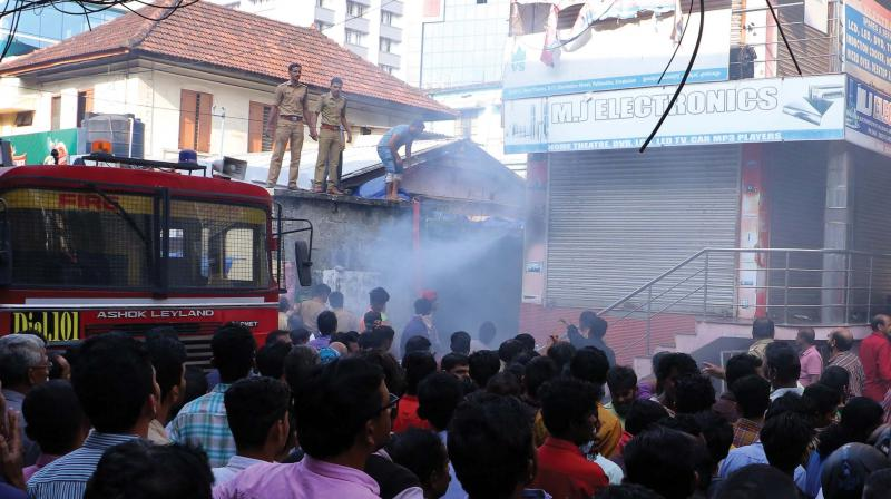 Fire and rescue force personnel douse the fire at Electronic street near Pallimukku in Kochi on Thursday. (Photo: DC)