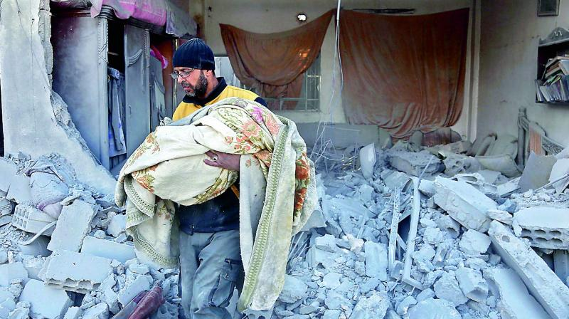 A member of the Syrian civil defence carries the body of a child out of a rubble in a house that was hit by a air strike in the rebel-held town of Jisreen. (Photo:AFP)
