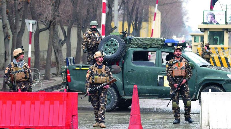 Afghan security personnel stand guard near the site of a suicide bombing in Kabul on Saturday.