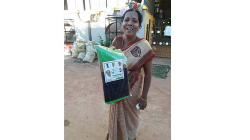 A woman with the saree given to her to attend the Congress convention in Hubballi on Monday. Photo:DC)