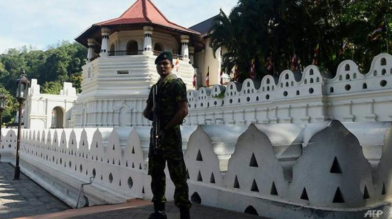 The government sent troops and elite police to Kandy after a mob set fire to a Muslim-owned shop, imposing a curfew there on Monday to prevent clashes between majority Sinhalese Buddhists and minority Muslims. (Photo: AFP)