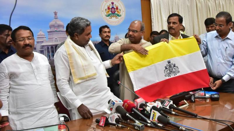 The Siddaramaiah-led Karnataka govt unveiled a yellow-white-and-red flag designed for the state at a meeting on Thursday. (Photo: @CMofKarnataka/Twitter)