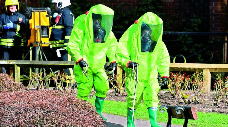 Members of the fire brigade in green biohazard suits work. (Photo:AFP)