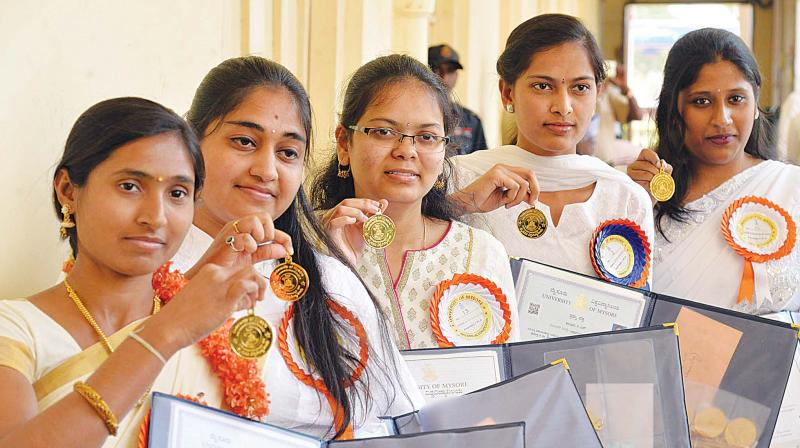 Graduating students strike a pose with their medals, in Mysuru on Monday. (Photo:KPN)