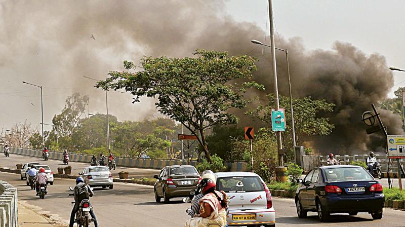 Huge cloud of smoke covering the Ring Road near Sumanahalli Flyover, causing problems to the residents and the motorists due to burning of garbage, in Bengaluru on Sunday.  (Photo:DC)
