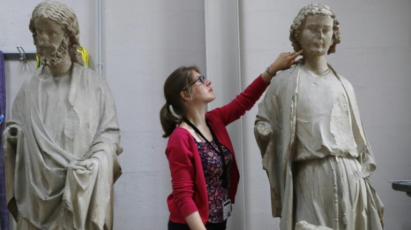 Heritage Curator of the Centre for Research and Restoration of Museums of France (C2RMF) Alexandre Gérard examines polychrome stone statues belonging to the Museum of Cluny, the