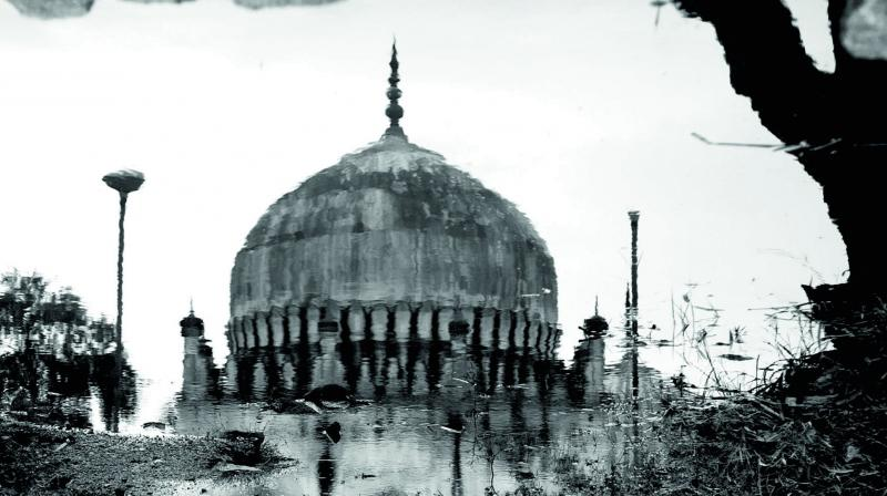 Reflection of one of the Qutb Shahi tombs post rains in a puddle of muddy rain water.