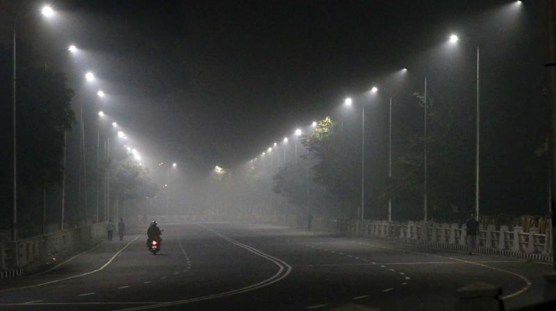 As pollution soars and temperatures dip, the city witnessed thick blanket of smog in the early hours of Friday. A scene on Kamarajar Salai at around 6.30 am on Friday.  	—DC