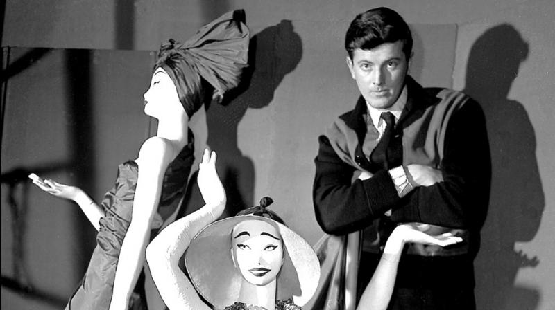 In this Feb.1 1952 file photo, French fashion designer Hubert de Givenchy poses with mannequins in his shop in Paris. French couturier Hubert de Givenchy, a pioneer of ready-to-wear who designed Audrey Hepburn's little black dress in
