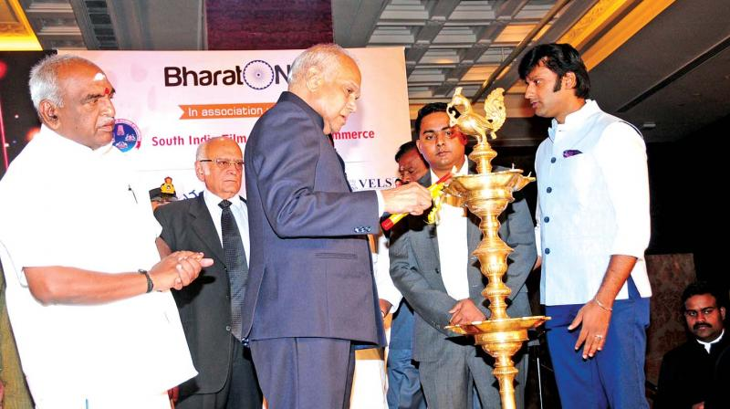 Governor Banwarilal Purohit lights the traditional lamp to inaugurate a conference on 'Indian Entertainment Industry: Global Leader in the Making' organised by Bharat Niti and the South India Film Chamber of Commerce, in the city on Saturday. Union minister of state for finance and shipping Pon Radhakrishnan looks on. (Photo: DC)