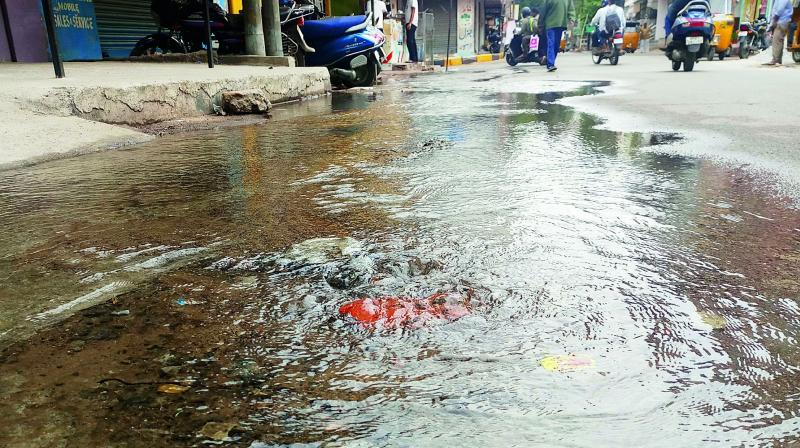 Water from a leaking pipeline spills on to the road at Kaladerain Malakpet.