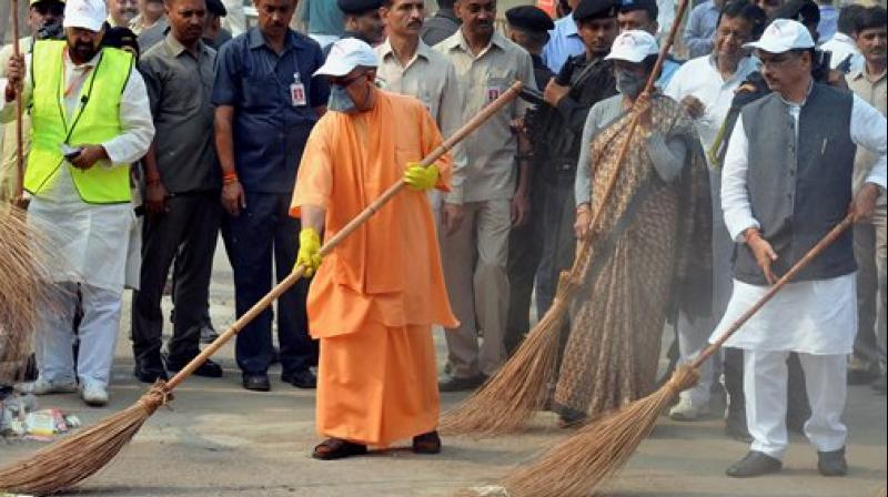 UP Chief Minister Yogi Adityanath weilds a broom as he takes part in a cleanliness drive at the western gate of the Taj Mahal in Agra on Thursday. Dy Chief Minister Dinesh Sharma and Tourism Minister Rita Bahuguna are also seen. (Photo: PTI)