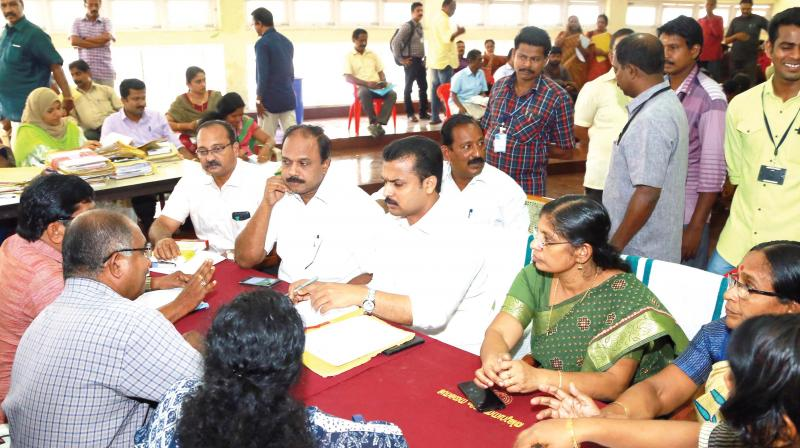 Mayor V.K. Prasanth listens to complaints as the building adalat is in progress on Monday. Corporation Secretary Deepa L.S, standing committee chairpersons Shafeera Beegum and Satheesh Kumar R, as well as Nanthancode councillor Palayam Rajan can be seen. (Photo: DC)