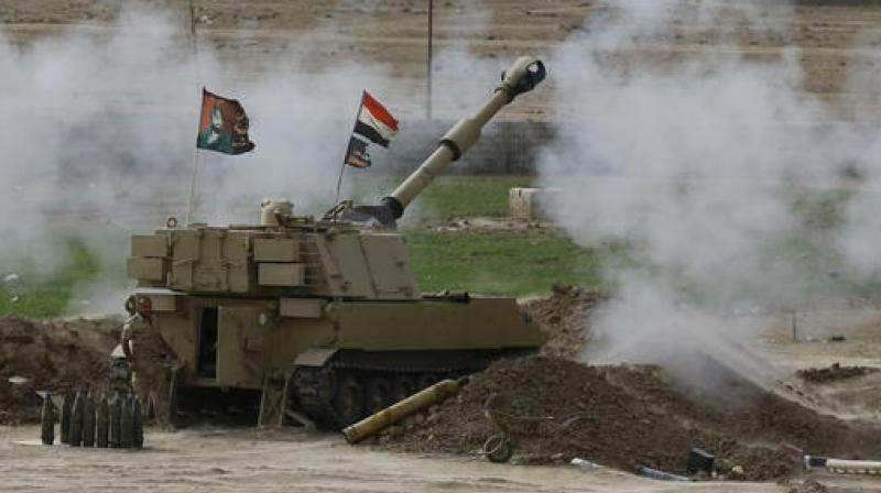 Iraqi soldiers fire a shell from a tank in the Iraqi village of Ali Rash toward Mosul in the fight against Islamic State militants. (Photo: AP)