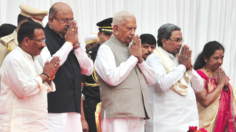Governor Vajubhai Vala, CM Siddaramaiah and the three newly inducted ministers R.B. Thimmapur, H.M. Revanna and Geetha Mahadevprasad at the swearing-in ceremony at Raj Bhavan on Friday