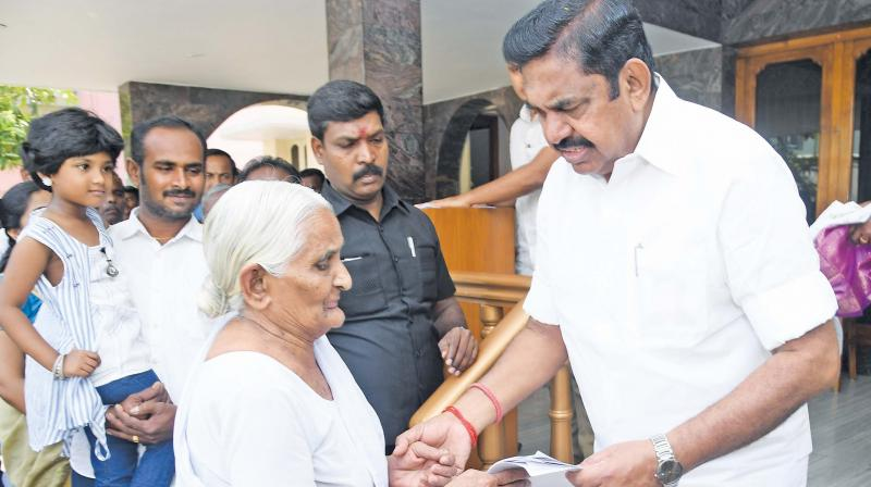 Tamil Nadu Chief Minister K Palaniswami receives a representation from an elderly woman in Salem on Sunday