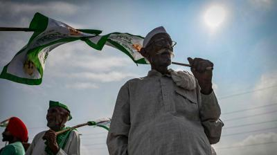 An elderly farmer holds a flag as he with others gather at the protest venue. (Representational Image/AFP)