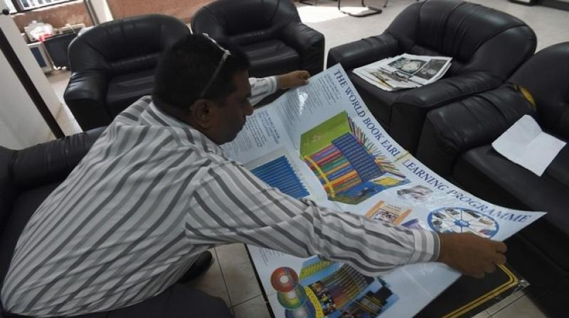 Indian salesman John Gunti displays explaining material about a children's learning programme he offers for sale, during a demonstration of his sales pitch in the Saudi capital Riyadh. (Photo: AFP)