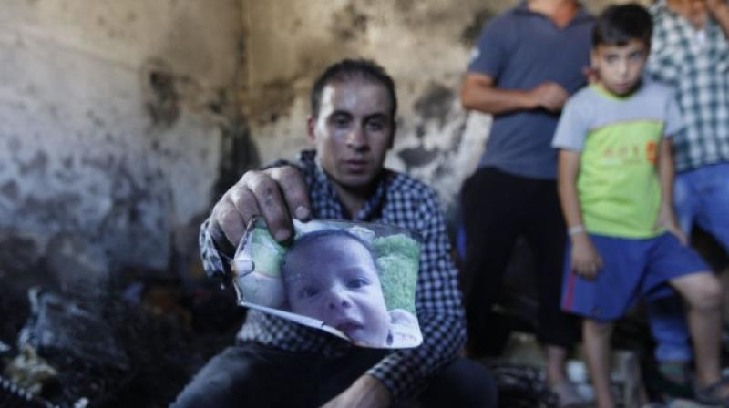 A relative holds up a photo of a one-and-a-half year old boy, Ali Dawabsha, in the family house torched in a suspected attack by Jewish terrorists in Duma village near the West Bank city of Nablus. (Photo: AP)