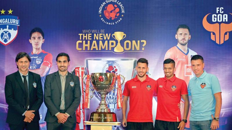 Bengaluru FC coach Charles Cuadrat (from left), midfielder Dimas Delgado, Goa FC player Coro, captain Mandar Desai and coach Sergio Lobera pose with winners' trophy of the Indian Super League in Mumbai on Saturday. (Photo: AP)