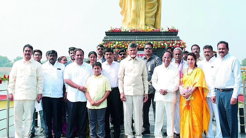 Chief Minister N. Chandrababu Naidu, AP Legislative Assembly Speaker K. Siva Prasad Rao and his family members pose for a photograph in front of 36ft NTR statue in Taraka Ram Sagar during its inaugural ceremony at Sattenapalli town of Guntur district on Friday. (Photo: DC)